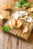 Головы чеснока с петрушкой на деревянном столе Стоковая Фотография