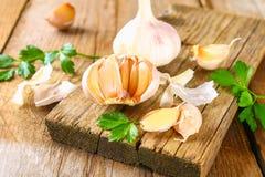 Головы чеснока с петрушкой на деревянном столе Стоковое Изображение