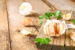 Головы чеснока с петрушкой на деревянном столе Стоковые Изображения