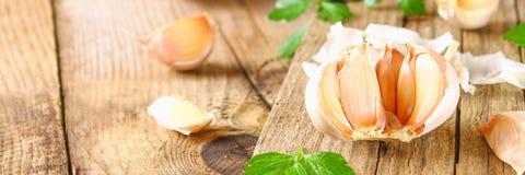 Головы чеснока с петрушкой на деревянном столе Стоковые Фото
