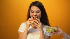 Голодная девушка выбирая гамбургер вместо салата, дешевой высококалорийной вредной пищи против здорового питания видеоматериал