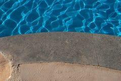 Голубая вода бассейна с волнами и гранитом Серый гранит всходя на борт к воде с отражением солнца Доска гранита бассейна и голубо Стоковое фото RF