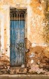 Голубая дверь закрыла за заржаветой решеткой металла на кирпичной стене с br Стоковое фото RF