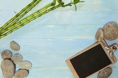Голубая деревянная доска с камешками и доской сзажимом для бумаги Стоковая Фотография