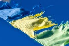 Голубая, желтая и зеленая тибетская буддийская молитва сигнализирует развевать в t Стоковое Изображение