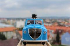 Голубая игрушка автомобиля в деревянном рельсе с blured городом в предпосылке Стоковые Изображения RF