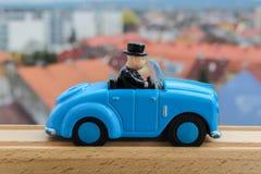 Голубая игрушка автомобиля от стороны в деревянном рельсе с blured городом в backgrou Стоковая Фотография