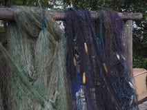 Голубая и зеленая рыболовная сеть повешенная на деревянной стойке стоковые фотографии rf
