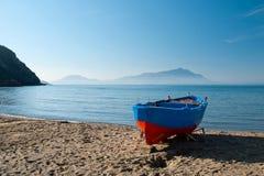 Голубая и красная шлюпка на пляже Стоковое Фото