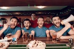 Голубая команда дует веселить на баре в баре спорт с унылыми красными вентиляторами команды в предпосылке Стоковые Изображения RF