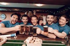 Голубая команда дует веселить на баре в баре спорт с унылыми красными вентиляторами команды в предпосылке Стоковая Фотография