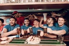 Голубая команда дует праздновать и веселить на баре в баре спорт с унылыми красными вентиляторами команды в предпосылке Стоковые Фотографии RF