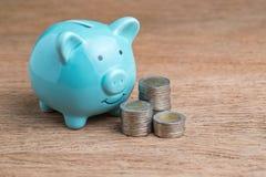 Голубая копилка и монетки штабелированные на деревянной таблице используя как финансы Стоковое Изображение