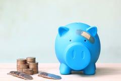 Голубая копилка прикрепленная в гипсолит на голове, сохраняет деньги для медицинского страхования и концепции здравоохранения стоковое изображение rf
