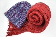 Голубая крышка зимы и красный шарф на белизне стоковые изображения