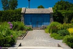 Голубая лачуга двери в саде стоковые изображения