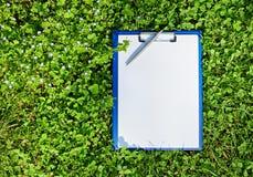 Голубая медицинская доска сзажимом для бумаги над зеленой травой Стоковые Фотографии RF