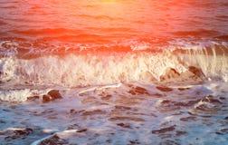 Голубая морская вода в оранжевом пирофакеле солнца Расслабляющий прибой волны моря над seashore Стоковые Изображения