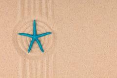 Голубая морская звезда лежит в центре круга песка лето seashells песка рамки принципиальной схемы предпосылки Стоковая Фотография RF