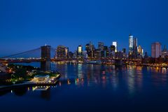 Голубая панорама Нью-Йорка с более низкими Манхаттаном и Бруклинским мостом Стоковые Изображения