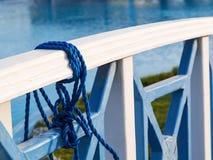 Голубая переплетенная веревочка связанная на перилах деревянного моста около озера, крупный план стоковое изображение rf