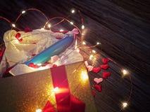 Голубая пластичная вибромашина фаллоимитатора в открытой подарочной коробке на черной деревянной предпосылке Стоковые Фото