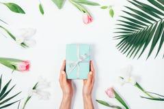 Голубая подарочная коробка в женских руках, ветви ладони, радужках и тюльпанах Стоковые Изображения