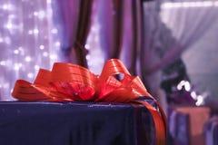 Голубая подарочная коробка с оранжевым смычком на празднике на темной предпосылке стоковые фотографии rf