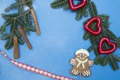 Голубая праздничная предпосылка с елевыми ветвями, пряником и украшениями Стоковая Фотография