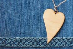 Голубая предпосылка джинсовой ткани, джинсы заплела пояс, деревянное сердце Стоковая Фотография RF