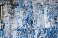 Голубая предпосылка с загубленными слезая бумагами Стоковое фото RF
