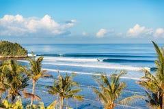Голубая разбивая волна в ладонях океана и кокоса на пляже Кристаллическая волна в Бали Стоковые Фотографии RF
