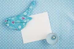 Голубая салфетка, карточка, деревянная птица и свеча, космос для текста Стоковые Фото