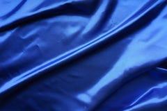 Голубая сатинировка, шелковистая ткань, волна, draperies Красивый фон ткани Конец-вверх Взгляд сверху Стоковое Изображение RF