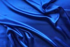 Голубая сатинировка, шелковистая ткань, волна, draperies Красивый фон ткани Конец-вверх Взгляд сверху Стоковая Фотография RF