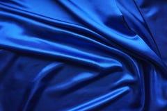 Голубая сатинировка, шелковистая ткань, волна, draperies Красивый фон ткани Конец-вверх Взгляд сверху Стоковое фото RF
