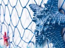 Голубая сеть и искусственные морские звёзды сделанные из пластмассы на стене декабре Стоковые Изображения