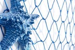 Голубая сеть и искусственные морские звёзды сделанные из пластмассы на стене декабре Стоковая Фотография
