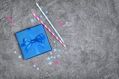 Голубая сияющая классическая подарочная коробка с соломами коктеиля смычка и бумаги сатинировки с confetti в форме звезд как атри стоковые фото