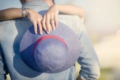 Голубая солома ` s женщины крупный план рук женщины обнимая человека снаружи Стоковое Фото