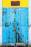 Голубая старая деревянная дверь с краской шелушения и большие повреждения, вход в желтой белизне покинули здание Стоковая Фотография RF