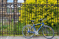 Голубая стойка велосипеда на замке на загородке металла grunge европейская улица велосипед самомоднейший Стоковое Изображение