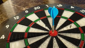 Голубая стрелка дротика яблочка ударяя центр цели dartboard Цель цели к концепции успеха стоковое изображение