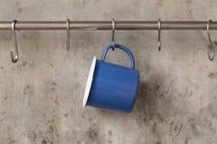 Голубая чашка олова вися на нержавеющем рельсе на предпосылке стены цемента стоковое фото rf