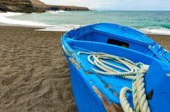 Голубая шлюпка на черном пляже Стоковая Фотография RF