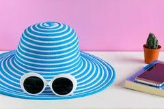 Голубая шляпа и белые солнечные очки украшают дырочками предпосылку стены стоковое изображение