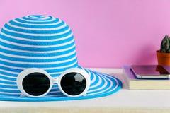 Голубая шляпа и белые солнечные очки украшают дырочками предпосылку стены стоковая фотография rf