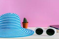 Голубая шляпа и белые солнечные очки украшают дырочками предпосылку стены стоковые изображения