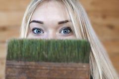 Голубоглазая блондинка шла сделать ремонт и решенный, что начало с красить стены с зеленой краской стоковые фото