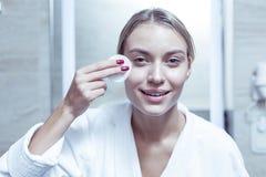 Голубоглазая симпатичная женщина извлекая макияж из стороны с пусковой площадкой хлопка стоковые фотографии rf